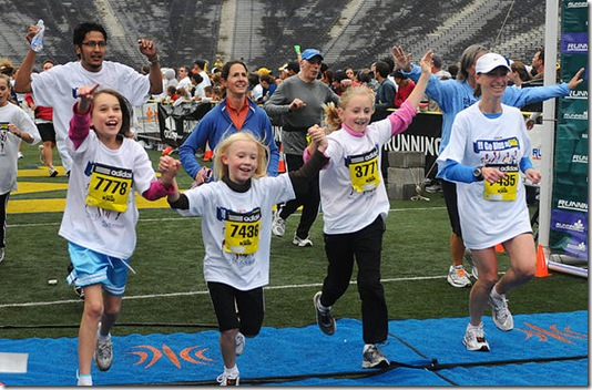 Runners young and old cross the finish line at the Big House Big Heart race yesterday. Participants had the option of running a 5K, 10K, or 1 mile fun run all raising money for heart health research. (MADDIE LAKIND/DAILY)